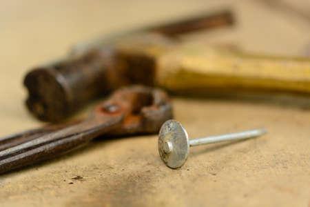 ferreteria: martillo, clavos y pinzas sobre fondo de madera Foto de archivo