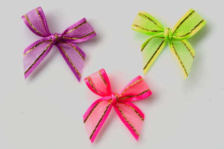 resent: pink, green, purple ribbon bow on white background