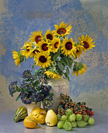 Still life with sunflowers in vase, other flowers and fruits