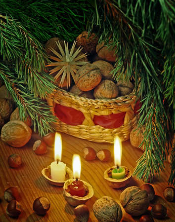 christmas still life with a nuts in basket and candles photo