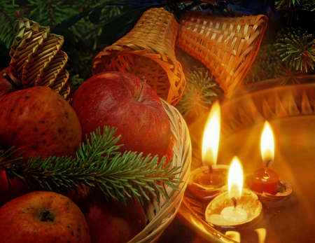christmas still life with an apples and candles floating in plate photo