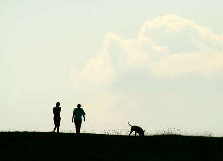 silhouette of two girls and a dog