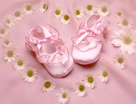 still life with a baby shoes surounded by flowers photo