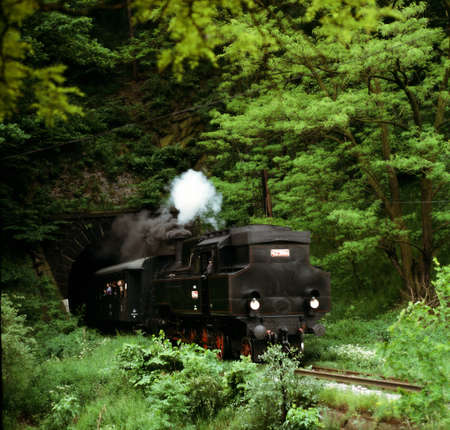 an old steam locomotive, which leaves from the tunnel photo