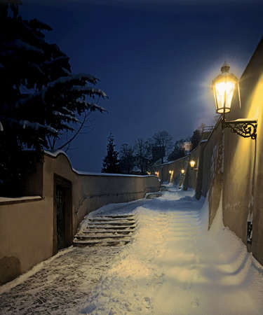 Night winter view on staircase leading to the castle, covered by snow.