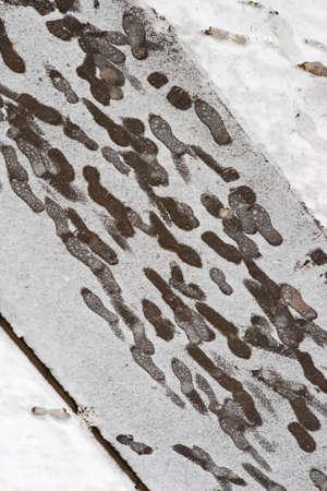 footprints at a snowy sidewalk