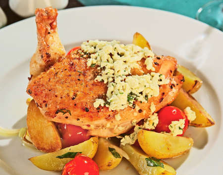 Chicken breast with roasted potatoes, grated cheese and tomatoes