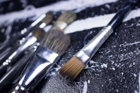 acrylic paint: paint brush on grungy black and white acrylic paint canvas