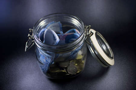 travel money glass jar world vacation planning currency photo Stock Photo