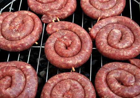broiling: Thuringian Bratwurst (round fried sausage) on a barbecue grill (german delicacy) Stock Photo