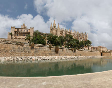 southern european descent: Cathedral La Seu in Palma de Mallorca, Spain. This church is one of the famous landmarks of Mallorca (Majorca). In the foreground Park del Mar. On the left side you can see the spanish kings palace Palau de lAlmundia