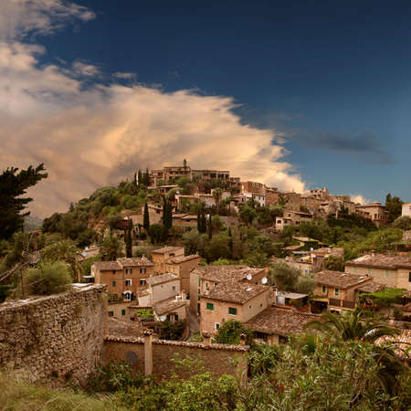 Mystic spirit - the hill of the picturesque and historic village Deia in the Tramuntana mountains (Mallorca, Spain) in engaging sunset light Stock Photo