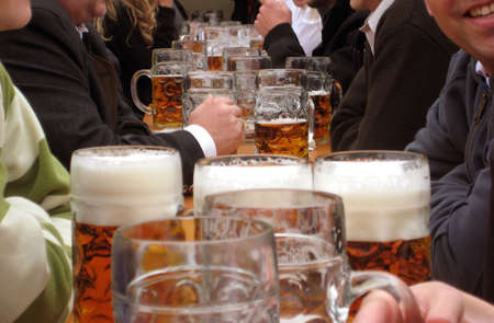 entertainment tent: Beeeer! Masskrüge, one liter beer mugs at the folk festival Oktoberfest in Munich in Germany. 6-7 millions of those mugs every year are sold t this world biggest fair. Stock Photo