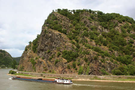 rhein: The legendary Loreley rock with the River Rhine (Rhein) and a container ship in Germany Stock Photo