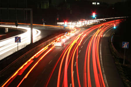 timelapse: Street at night - Time exposure photo (30 seconds) with a street at night and automobile headlights of a multiple lane city street and a traffic light, seen at the Autobahn near Auestadion in Kassel, Germany