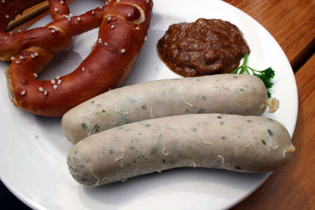 veal sausage: A typical Bavarian veal sausage with Pretzel (Brezn) and sweet mustard on a plate, should be in Bavaria traditional eaten before noon Stock Photo