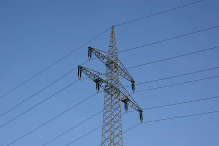 communications tower: Power line in front of blue sky Stock Photo