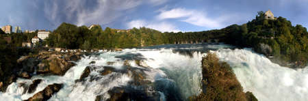 near side: Rhine falls near Schaffhausen. 200� panoramic picture of the biggest European waterfall in Switzerland. On the right side Castle Lauffen.