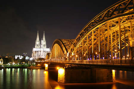 Illuminated Cologne dome, river Rhine and Deutz bridge at night