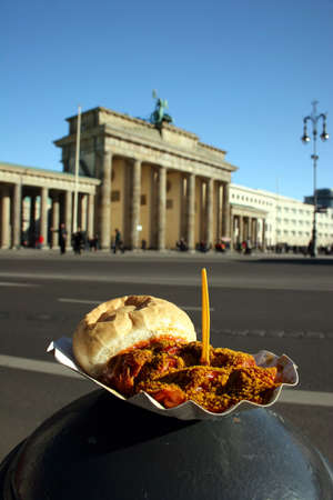 One of Germanys typical and most popular meals, the Berlin Currywurst (sausage with curry sauce) in front of the most famous landmark of Germany, the Brandenburg Gate in Berlin.