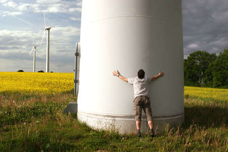 Man embraces a Windmill in front of a rape field photo