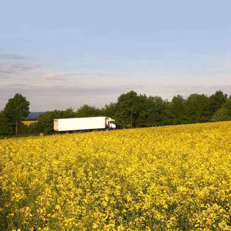 White truck behind a bright rape field, seen near Kassel, Germany