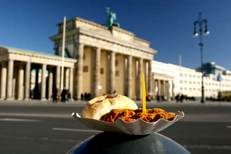 east germany: One of Germanys typical and most popular meals, the Berlin Currywurst (sausage with curry sauce) in front of the most famous landmark of Germany, the Brandenburg Gate in Berlin.