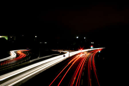 Time exposure photo (30 seconds) with a street at night and automobile headlights of a multiple lane city street and a traffic light, seen at the Autobahn near Auestadion in Kassel, Germany photo