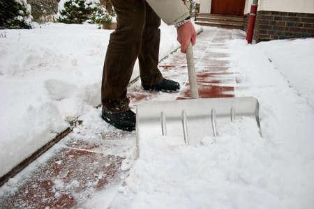 Man shoveling snow at a footpath photo