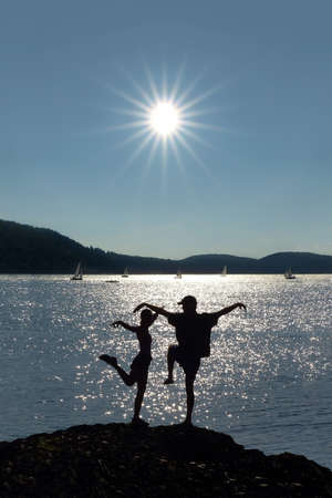 Acrobatic couple in front of sun and lake (Edersee in Germany) photo