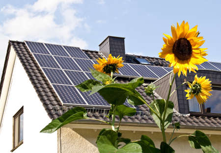 yellow house: Solar cells on a roof with sun flowers in the foreground