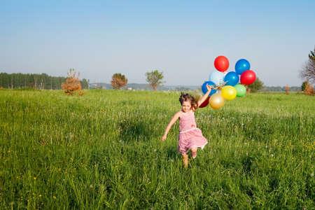 ballons: little girl runs with multicolored balloons