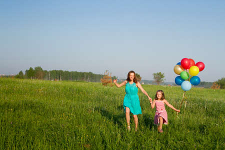 Mother and daughter with multicolored balloons