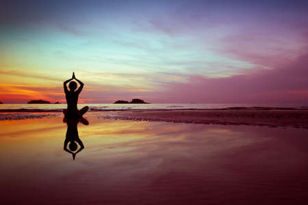 woman practices yoga on the beach at sunset