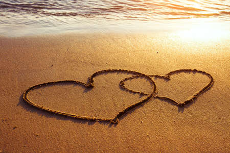 sand beach: honeymoon or valentine s day greetings on the sand, two hearts Stock Photo