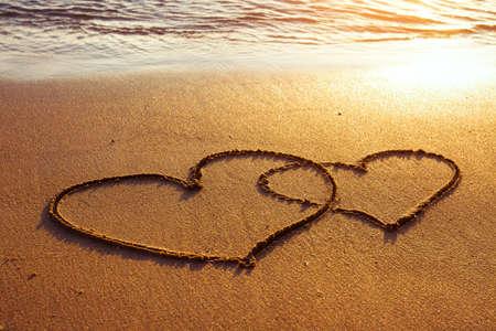 parejas de amor: luna de miel o San Valent�n s saludos del d�a en la arena, dos corazones Foto de archivo