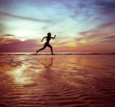 scamper: woman runs, silhouette on the beach at sunset