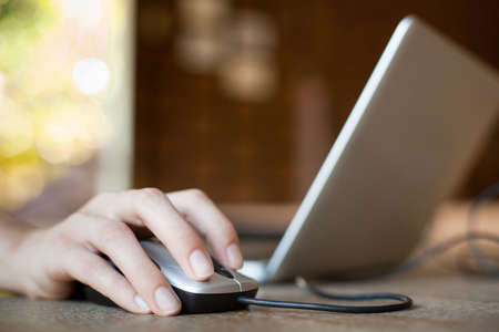 マウスをクリックして、マウスとノート パソコンでの女性の手 写真素材