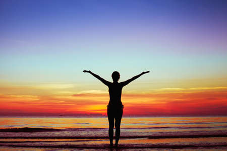 healthy lifestyle background, silhouette of woman with raised hands on the beach at sunset Archivio Fotografico
