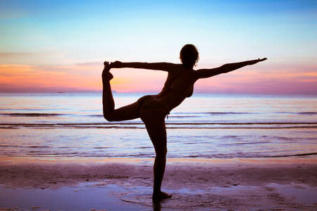 silhouette of young woman doing gym and stretch exercises on the beach photo