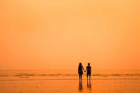 sunset silhouettes of loving couple on the beach