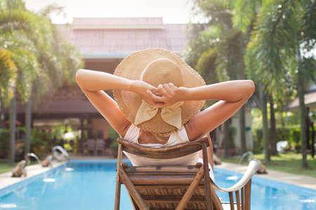 woman in hat taking sunbath near swimming pool photo