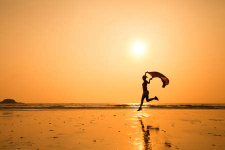 silhouette of happy running woman on the beach Stok Fotoğraf