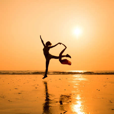 woman beach dress: silhouette of dancing woman on the beach Stock Photo