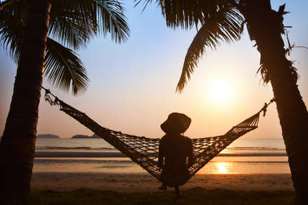 travel locations: silhouette of woman in hat sitting in hammock at sunset on the beach Stock Photo