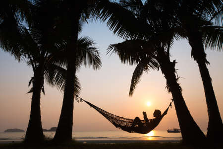 relaxamento: silhueta da mulher na rede ao pôr do sol na praia Imagens