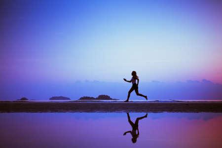 proposito: de fondo el deporte, corre a propósito, silueta de mujer en la playa Foto de archivo