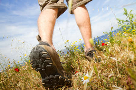 shoes off: young tourist backpacker walking through green meadow in trekking shoes Stock Photo