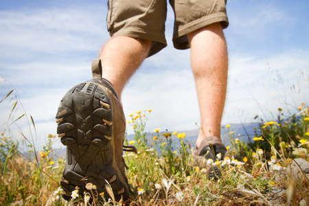 shoes off: trekking shoes, backpacker walking through green meadow