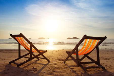 strand, twee ligstoelen en een blauwe lucht